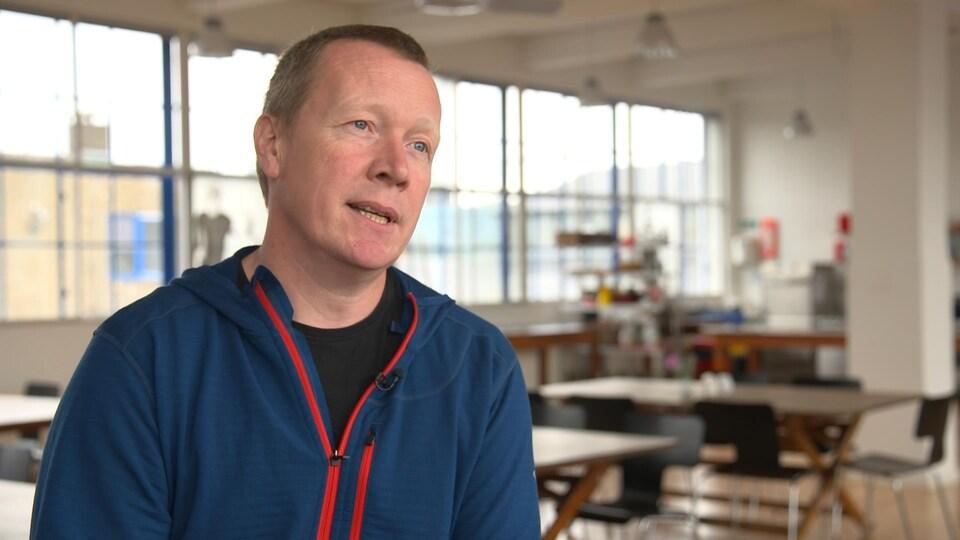 On voit M. Højgaard parler à la caméra avec en arrière-plan les tables et fenêtres des locaux de Madhus, à Copenhague, au Danemark.