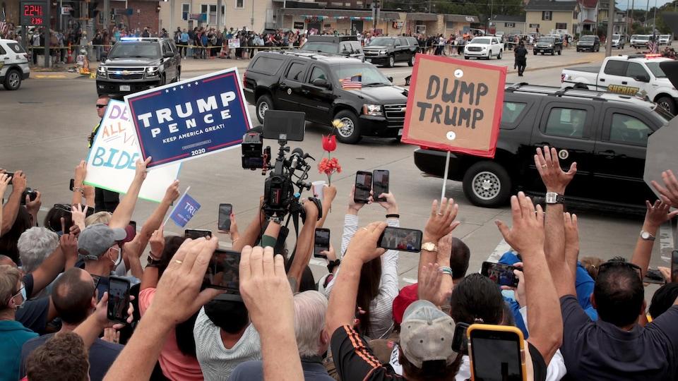 Tandis que le convoi présidentiel circule sur la rue, des dizaines de personnes se tiennent près du chemin, pancartes à la main.