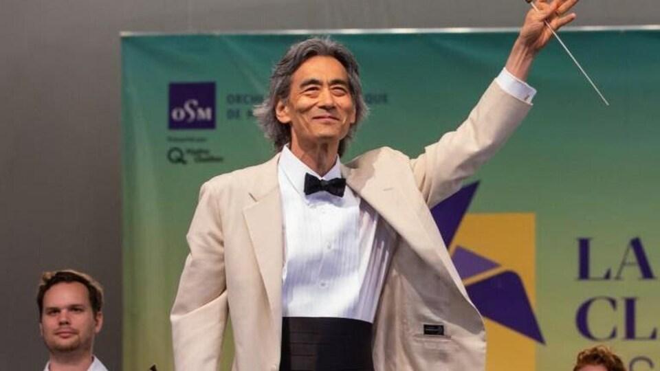 L'homme salue la foule et tient sa baguette dans la main. Il est entouré de musiciens et de musiciennes.