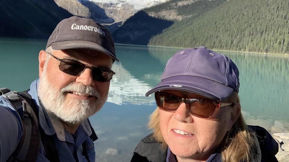 Un égoportrait de Kerry et Cheryl Guy devant un lac bleu dans les montagnes.