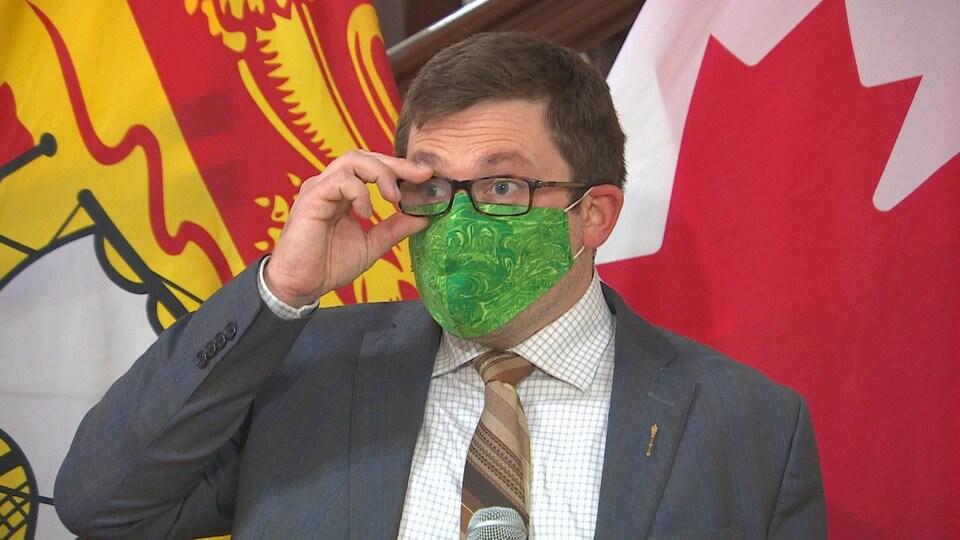 Kevin Arseneau porte un masque et participe à une mêlée de presse et ajuste ses lunettes.