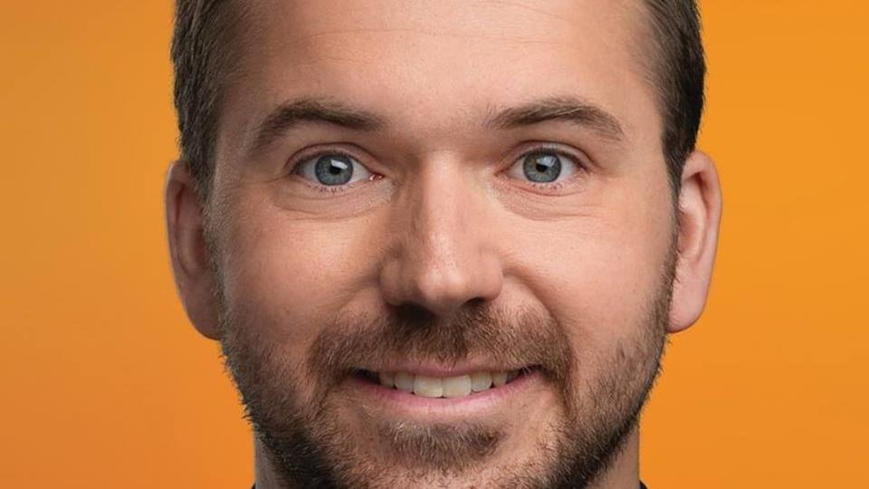 Une jeune homme dans la trentaine en gros plan. Il a les cheveux bruns courts. Il a les yeux bleus. Il sourit à la caméra.
