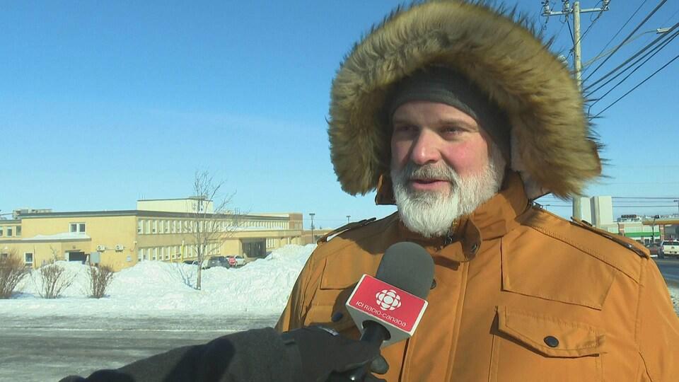 À l'extérieur et vêtu d'un manteau d'hiver à capuchon de fourrure, le maire donne une entrevue au micro de Radio-Canada.