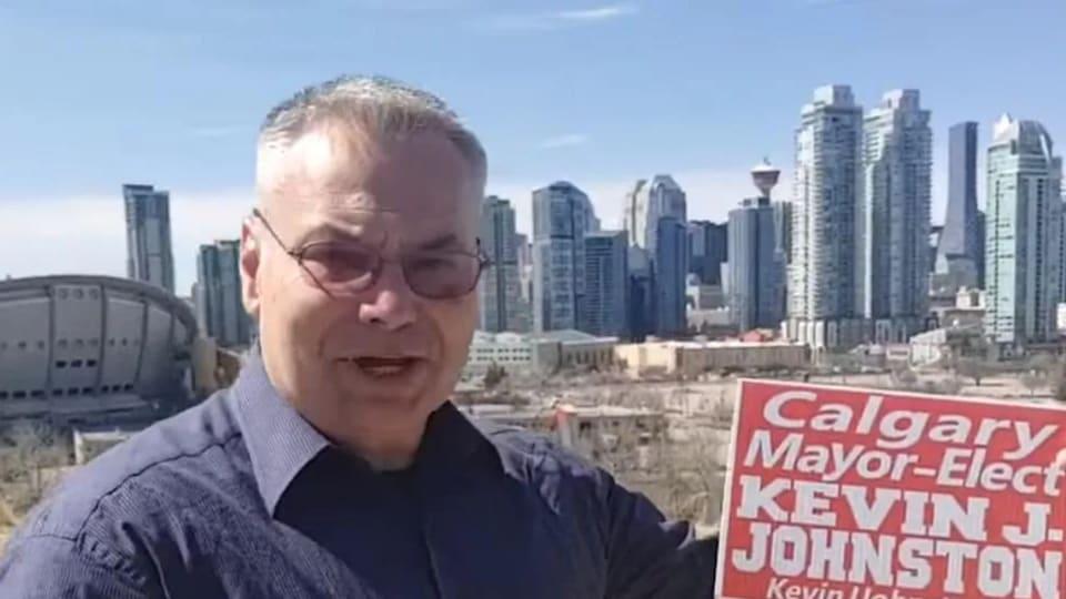 Kevin J. Johnston pose devant la ville de Calgary, une pancarte électorale à la main.