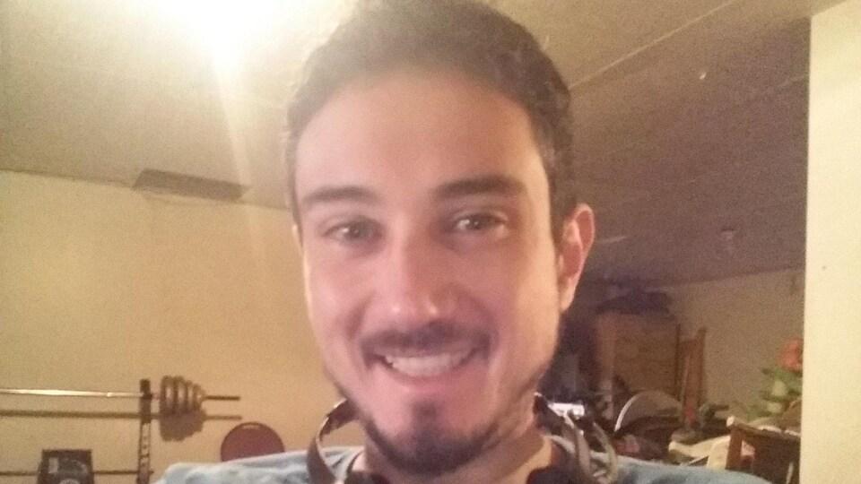 Un homme se prend en photo avec la caméra de son ordinateur, souriant.