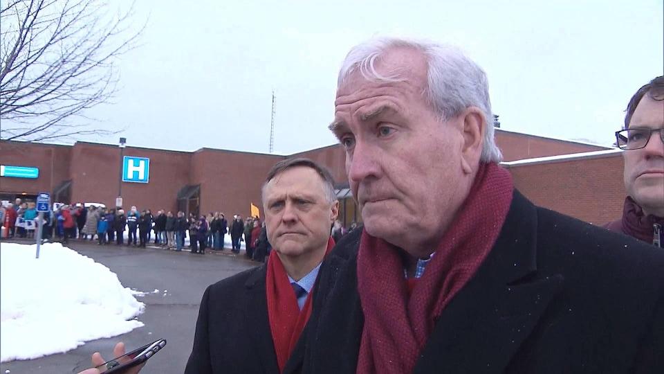 Kevin Vickers à l'extérieur devant l'hôpital où des gens manifestent.