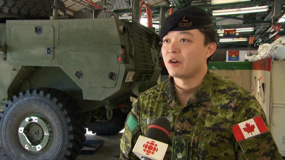 Kevin Wong en entrevue devant un véhicule des Forces armées canadiennes.