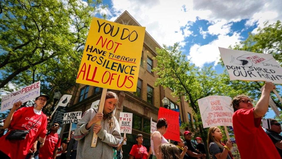 Des manifestants tiennent des pancartes pendant une marche dans la rue.