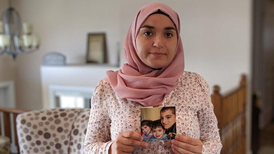 Une femme portant un foulard sur la tête tient une photo de ses enfants.