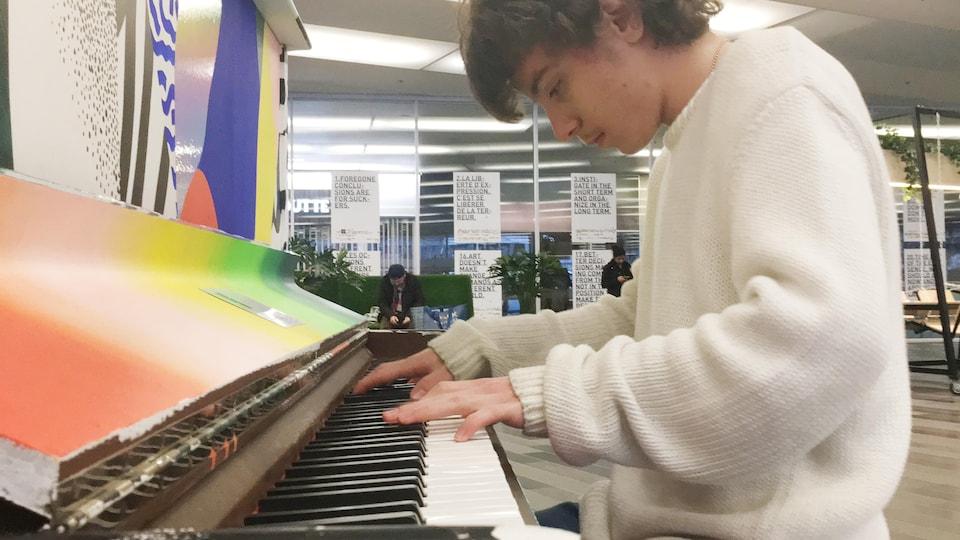 Le jeune pianiste Kian Nojoumian jouant sur un piano public au Palais des congrès de Montréal.