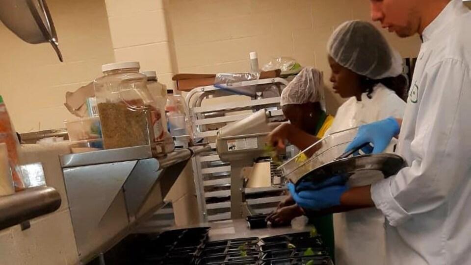 Trois cuisiniers préparent des boîtes à lunch.