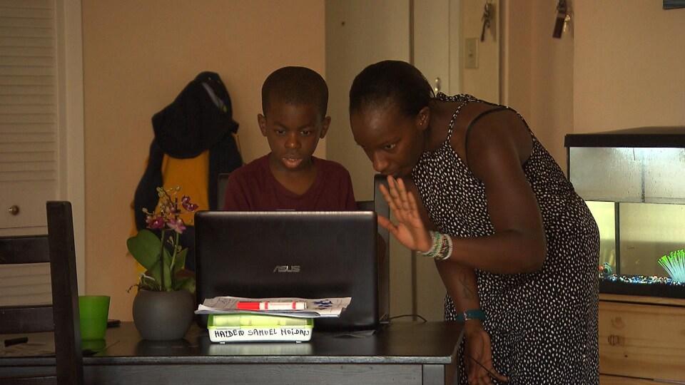Mme Couliaby et son fils Yanis regardent l'écran d'un ordinateur portable.