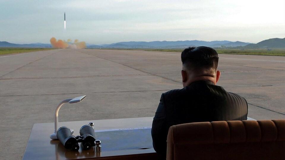 Kim Jong-un, de dos, observe un tir de missile assis à son bureau.