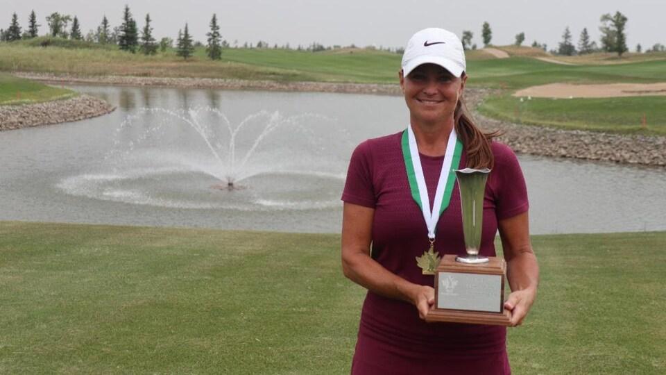 Kim Walker, vêtue d'une casquette sur un terrain de golf, sourit et porte une médaille au cou, tenant son trophée de championne du tournoi de golf.