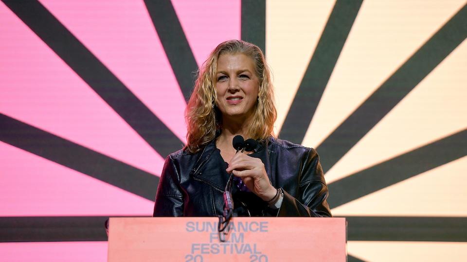 La femme parle sur la scène, devant un micro.
