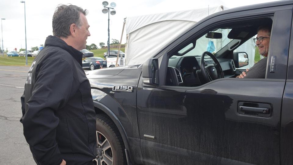 Dennis King debout parle à un homme souriant au volant d'une camionnette.