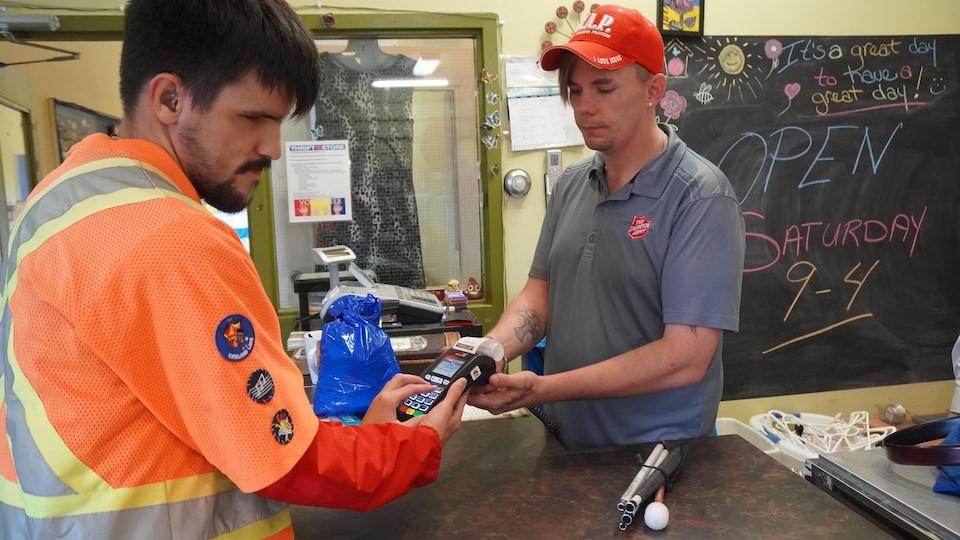 Un caissier remet une machine de débit dans les mains d'une personne aveugle.