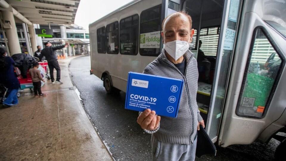 Un voyageur présente un kit de test COVID-19 à domicile.