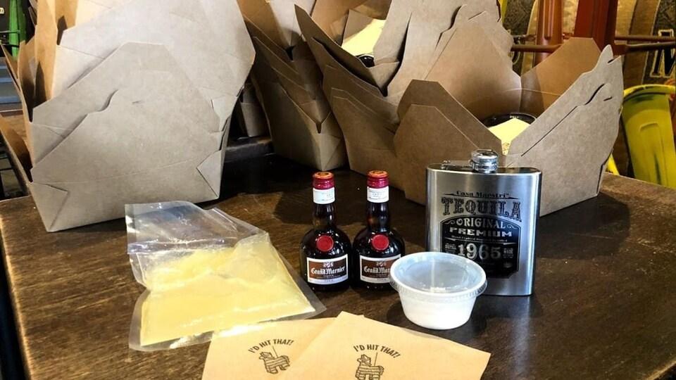 Un sac plastique rempli de jus de citron, deux petites bouteilles de Grand Marnier, une flasque métallique de téquila et un petit pot contenant du sel sont placés sur une table en bois. Il y a aussi des boîtes en carton à l'arrière-plan.