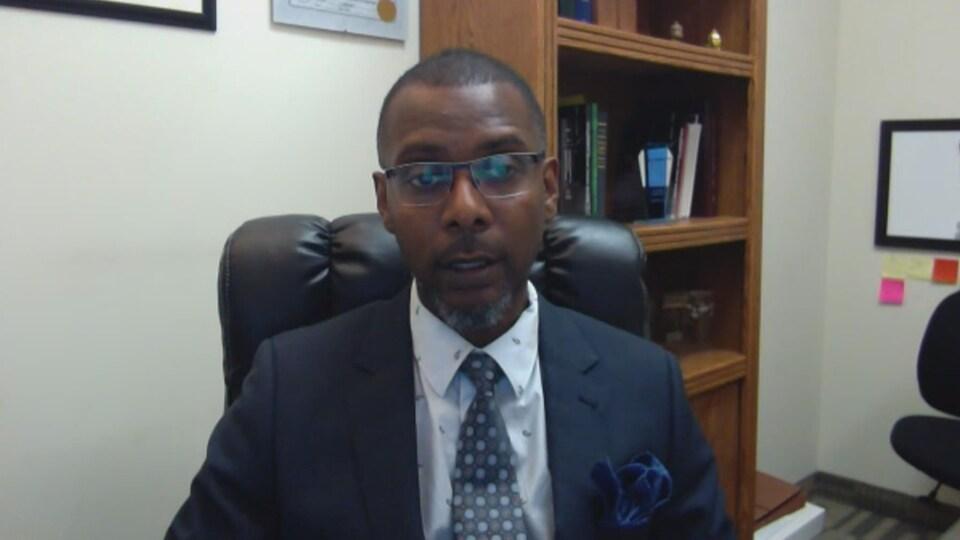 Un homme noir, portant des lunettes, vêtu d'un complet cravate, assis dans un bureau devant un écran.