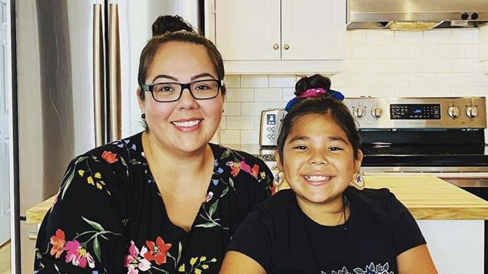 Une dame autochtone pose avec sa fille à la table de cuisine.