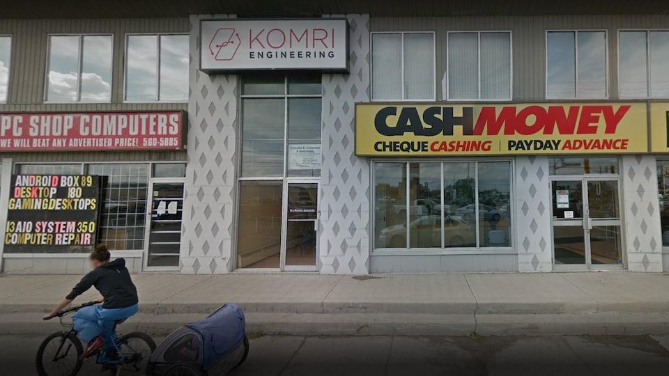 Une rue passante avec des immeubles, on peut voir une enseigne lisant Komri Engineering sur une façade.