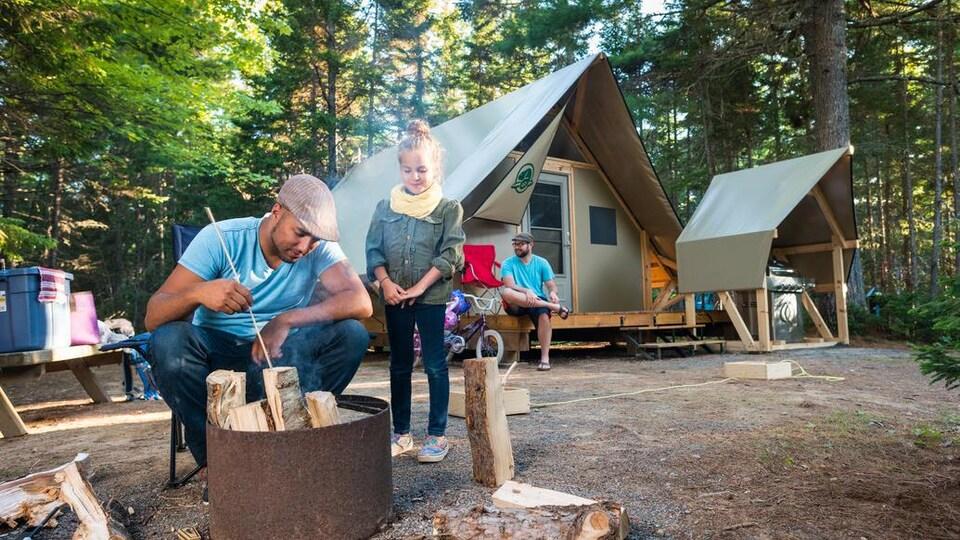 Un homme et une fillette sont devant un feu avec une tente et un autre homme en arrière-plan.
