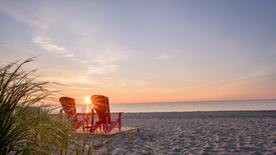 Des chaises rouges sur la plage Kellys alors que le soleil se lève.