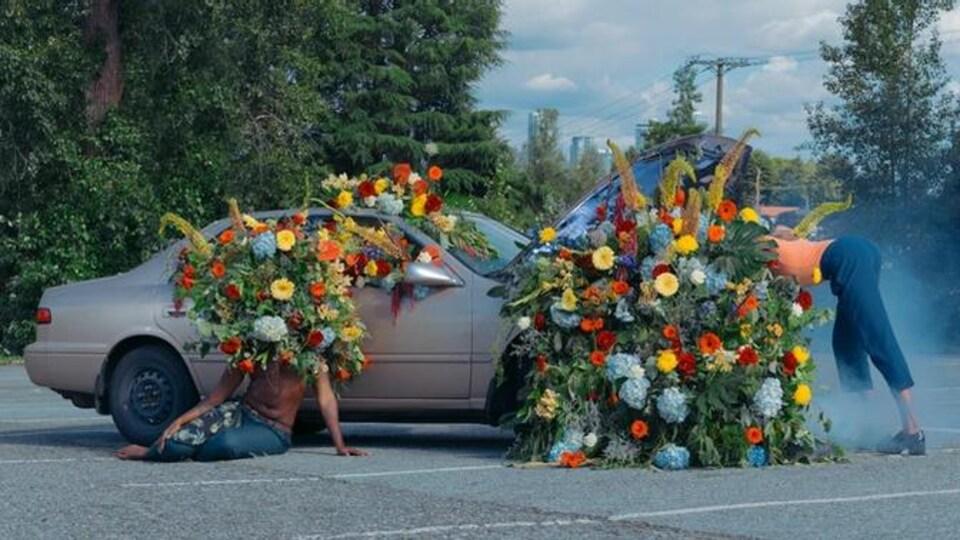 une voiture en panne remplie de fleurs. une personne est assise devant, avec des fleurs à la place de la tête, l'autre est penchée sur le moteur.