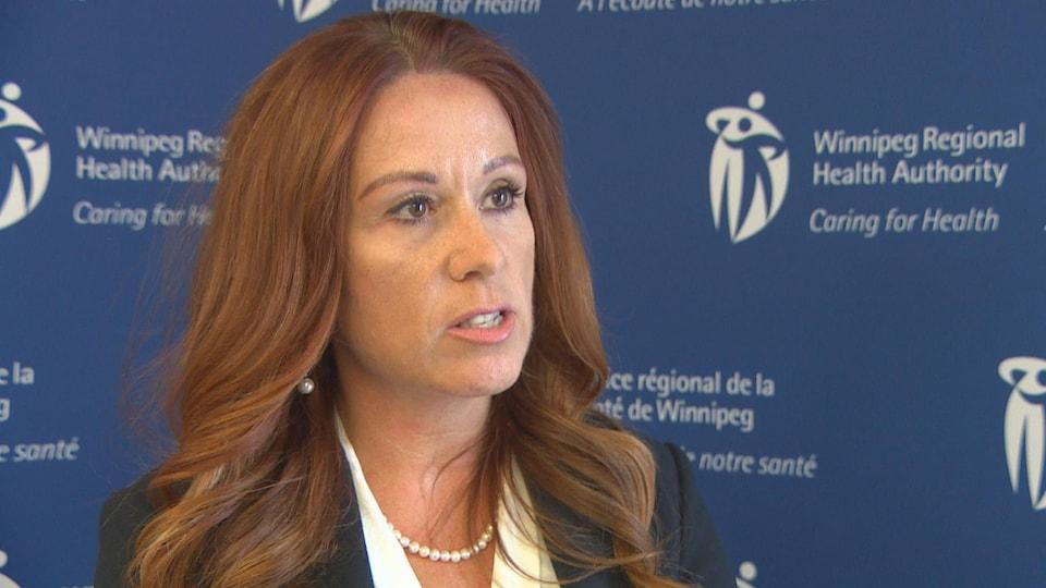 Une dame aux longs cheveux roux s'exprime devant la caméra.
