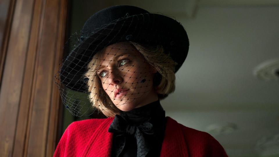 Une femme blonde porte un manteau rouge et un chapeau noir.