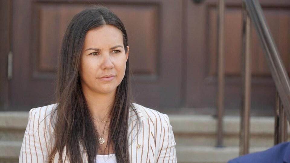 La politicienne porte un veston. Son regard est tourné vers le chef du Bloc Québécois.