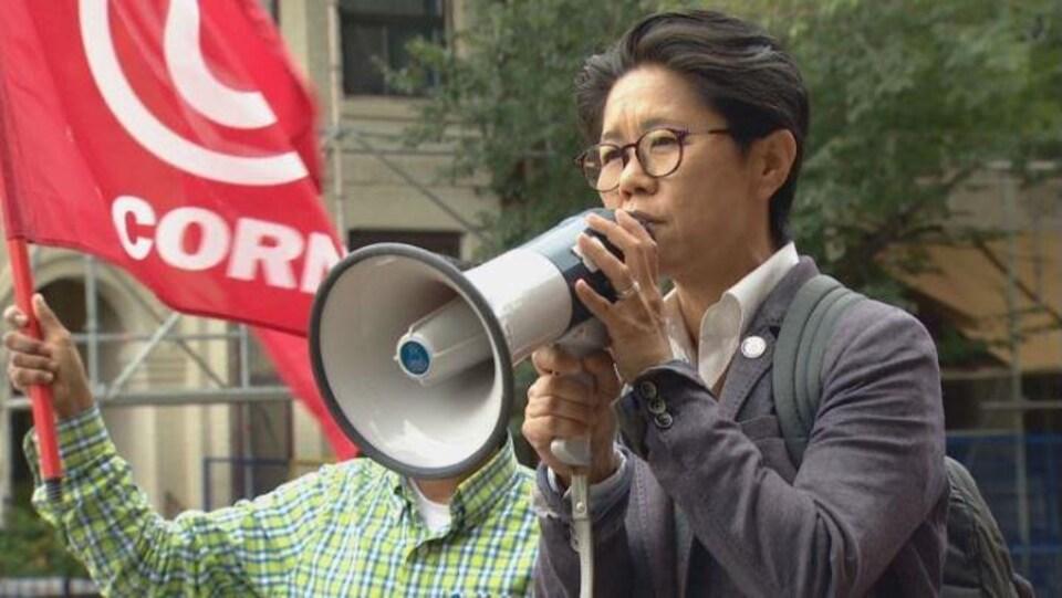 Une femme avec des lunettes et tenant un mégaphone