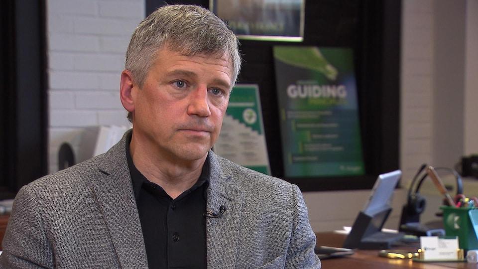 Un homme portant un veston gris regarde le journaliste lors d'une entrevue dans son bureau.