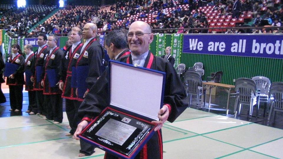 L'homme souriant tient une boîte ouverte dans laquelle se trouve un cadre. D'autres athlètes se trouvent dans un gymnase devant plusieurs spectateurs.
