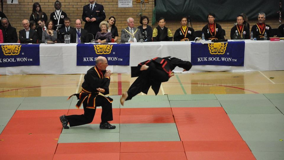 Deux hommes s'affrontent sur des tapis devant public dans un gymnase.