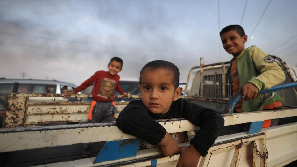 Trois enfants à l'arrière d'une voiture.