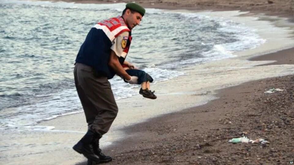 L'homme marche sur la plage avec le petit garçon de 3 ans dans ses bras