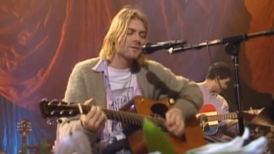 Kurt Cobain porte un cardigan vert olive et joue de la guitare.