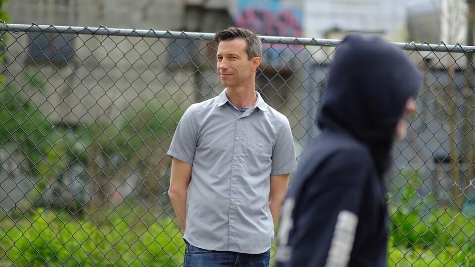 Kurt Lock debout devant une clôture.