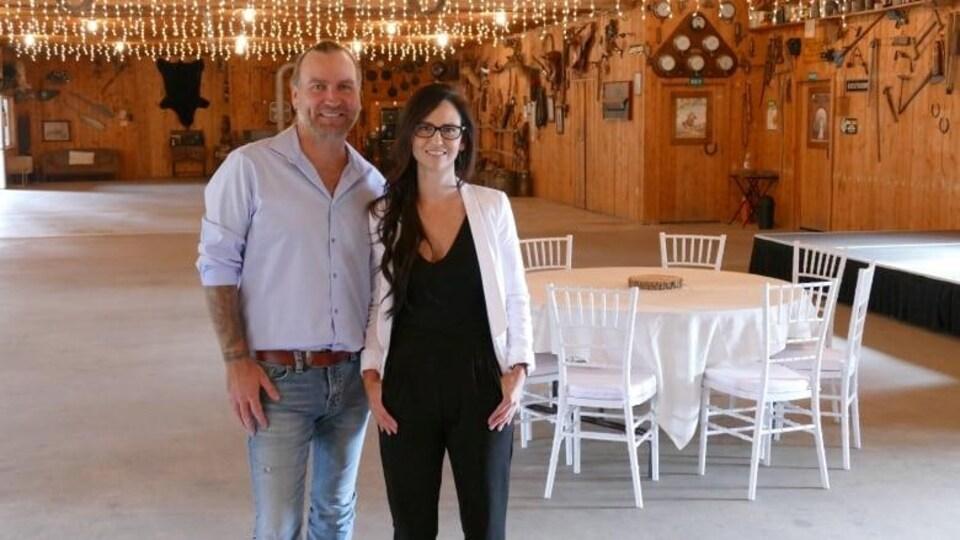 Un couple, Kyle et Louise Anderson, propriétaire du ranch Hitch N' Post, pose dans une salle de réception de mariage.