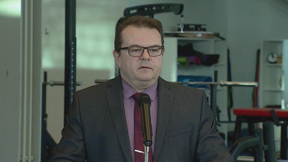 Kyle Ripley se tient à un podium devant une salle de conditionnement physique.