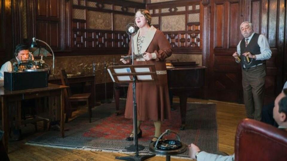 L'actrice Debbie Lynch-White chante devant un micro et un lutrin dans un salon.