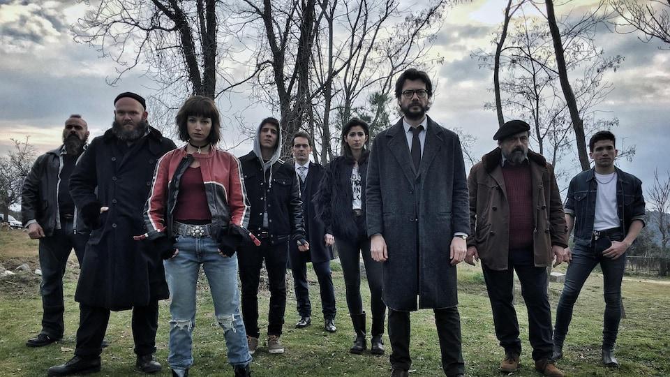 Les personnages de la série <i>La casa de papel</i> se tiennent debout dans un champ, regardant la caméra.