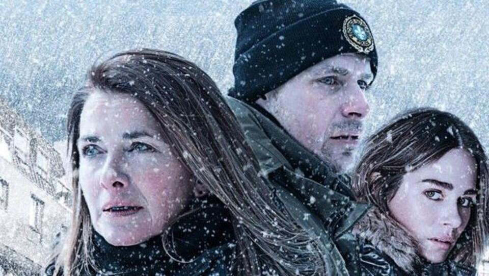 Un homme entouré de deux femmes sous la neige