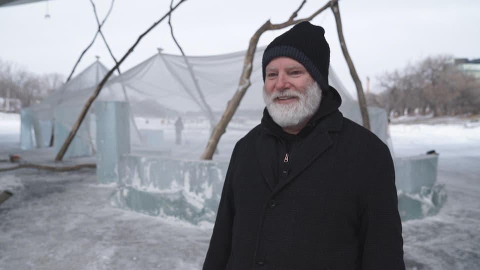 Un homme dehors, sur la glace d'une rivière gelée avec derrière lui une sorte de tente faite de blocs de glace desquels s'élèvent des troncs d'arbre qui supportent une toile transparente.