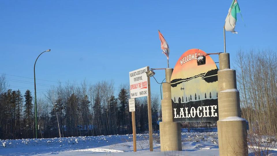 Un panneau indique la limite du village de Laloche sous un ciel découvert.