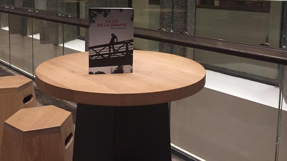 Le livre est posé sur une table à la surface de bois clair, dans un espace vitré, avec un sol en béton. Sur la couverture, on voit la silhouette d'une personne se retenant à une rampe, sur un pont.
