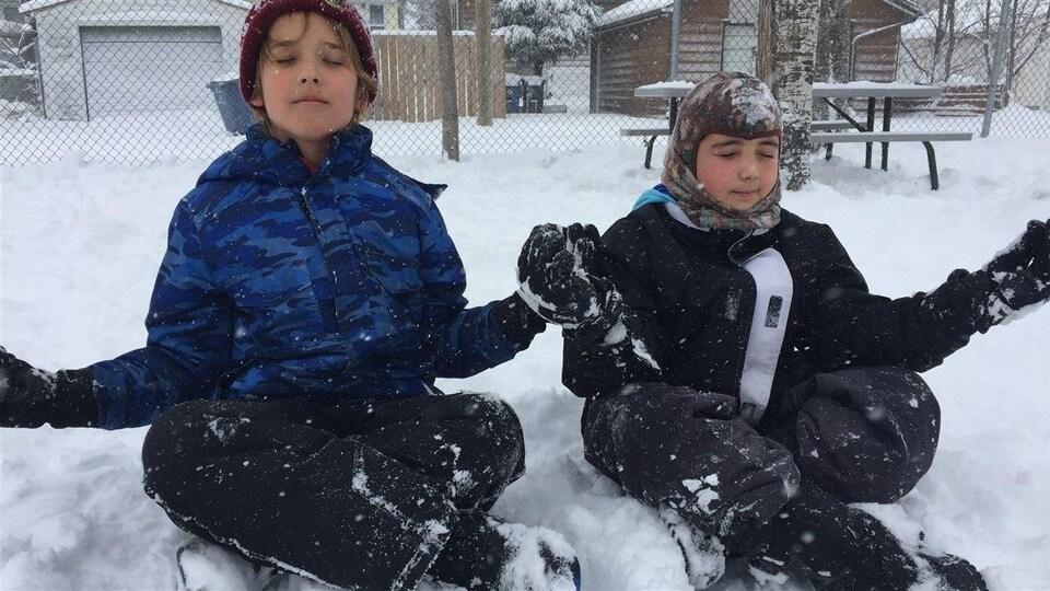 Des enfants assis dans la neige