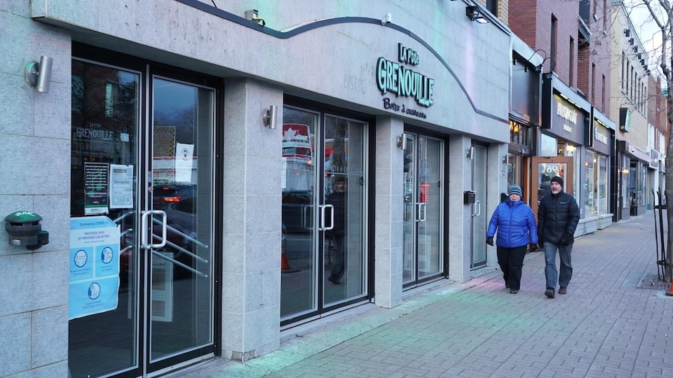 Des passants marchent devant La P'tite Grenouille, à Rimouski.